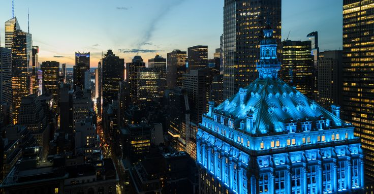 Photo of the Helmsley Building lit up blue in honor of essential workers (via RXR Realty)